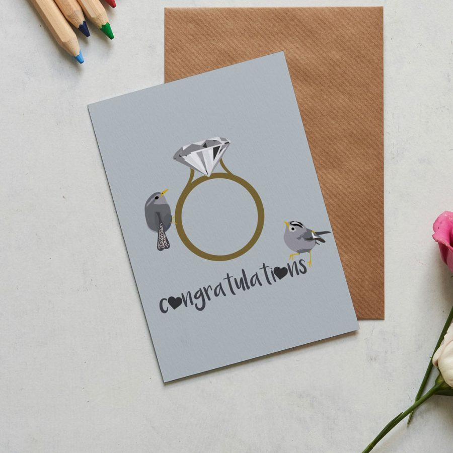 This Congratulations card is perfect for those that have just got engaged, or for a wedding. The illustration shows a giant diamond ring with love birds perched within in the words